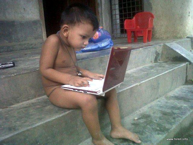 Little kid without clothes, playing with laptop.